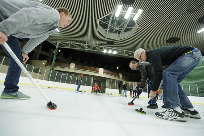 Lilac City Curling Club member Jon Escott, second from the right, instructs students Reed Cody, left, and Dave Jackson on proper sweeping technique. - YOUNG KWAK