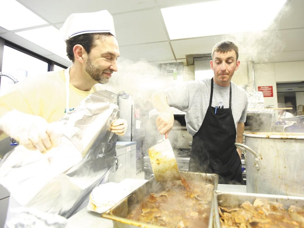 Lloyd Halpern, left, watches Jordan Bressler pour sauce onto brisket. - YOUNG KWAK