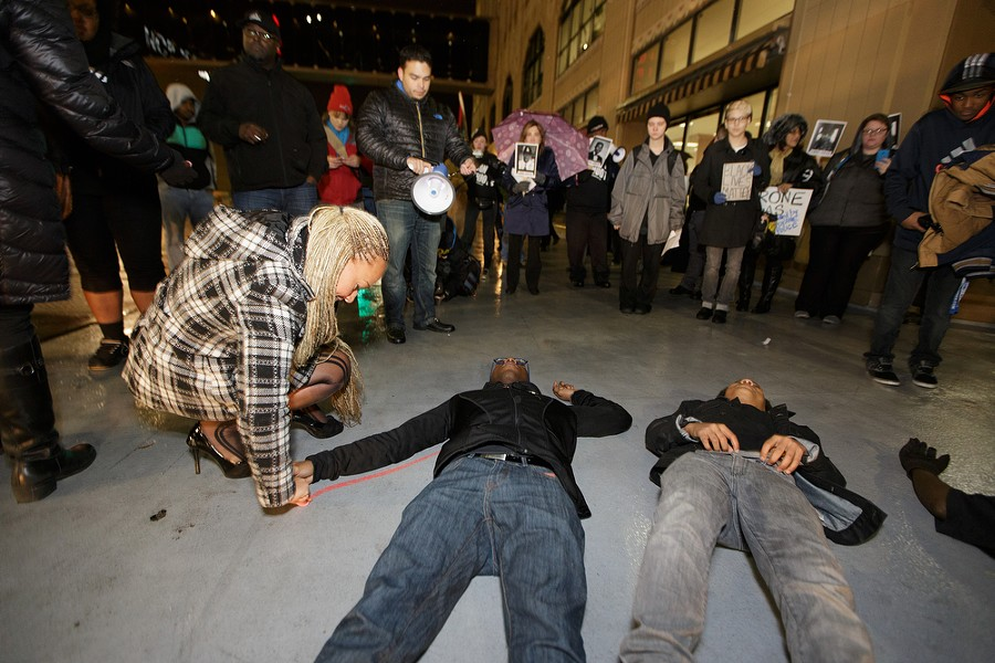 """Local NAACP chapter President and Inlander commentary contributor Rachel Dolezal, left, draws a chalk outline around her 20-year-old son Isaiah Dolezal as part of a """"die-in"""" in front of City Hall. - YOUNG KWAK"""