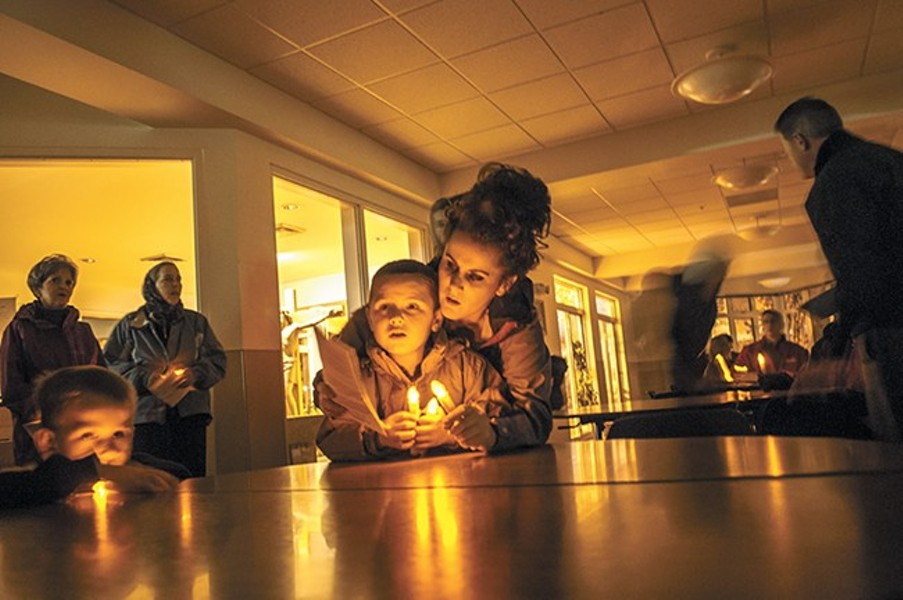 """Christina Napier helps 5-year-old Jordan Jensen read Christmas hymns during a """"Candlelight Vigil Against Poverty"""" with Catholic Charities Spokane in November. - SARAH WURTZ"""