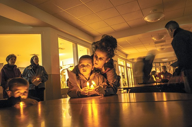 "Christina Napier helps 5-year-old Jordan Jensen read Christmas hymns during a ""Candlelight Vigil Against Poverty"" with Catholic Charities Spokane in November. - SARAH WURTZ"