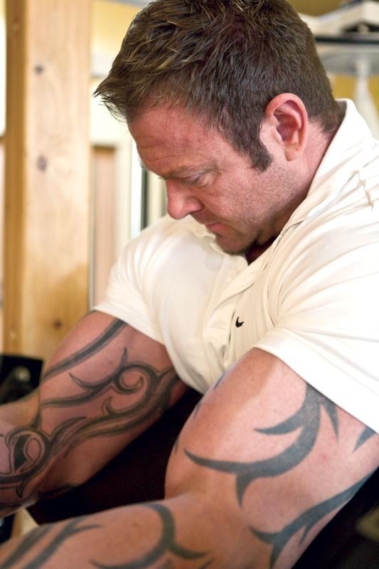 Marcell Scott works his biceps at H.I.T. Fitness, his training studio in Spokane. - STEPHEN SCHLANGE