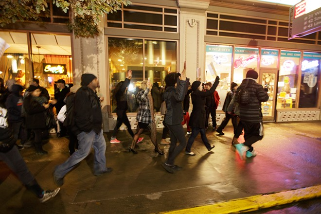 Marchers approach the STA Plaza on W. Sprague Ave. - YOUNG KWAK