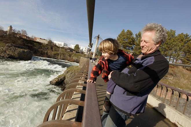 Mark Solomon holds his 3-year-old son Alex on the suspension bridge to view the Spokane River. - YOUNG KWAK