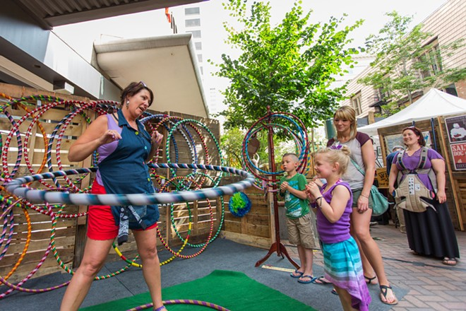 Michelle Heyn, left, of Rock Rings Hula Hoops demonstrates her skill to children. - MATT WEIGAND