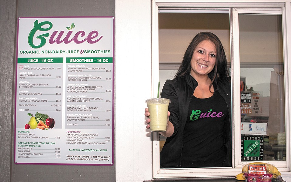Michelle Kinyon serves an organic juice from Guice's drive-through. - ASHLEY TOMLINSON