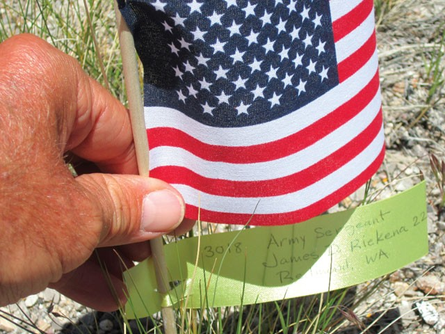Mike Ehredt places a flag in memory of James Riekena, the 3,018th American soldier to die in Iraq, at milepost 11 along Highway 287 near Rawlins, Wyo., last week. - MIKE EHREDT
