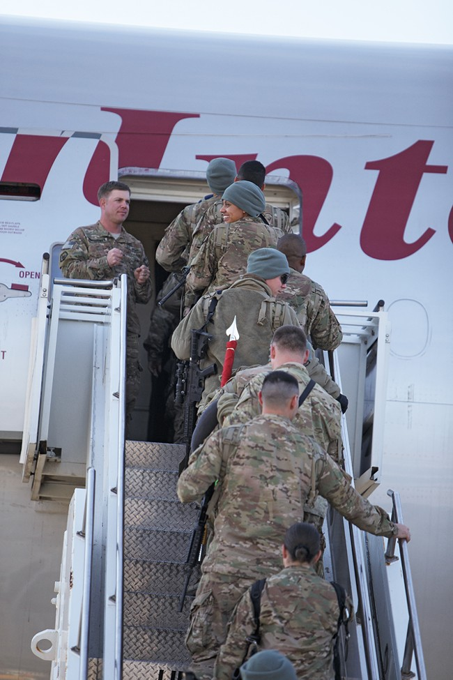 Military personnel returning from combat deployment in Afghanistan board an airplane to go home. - YOUNG KWAK