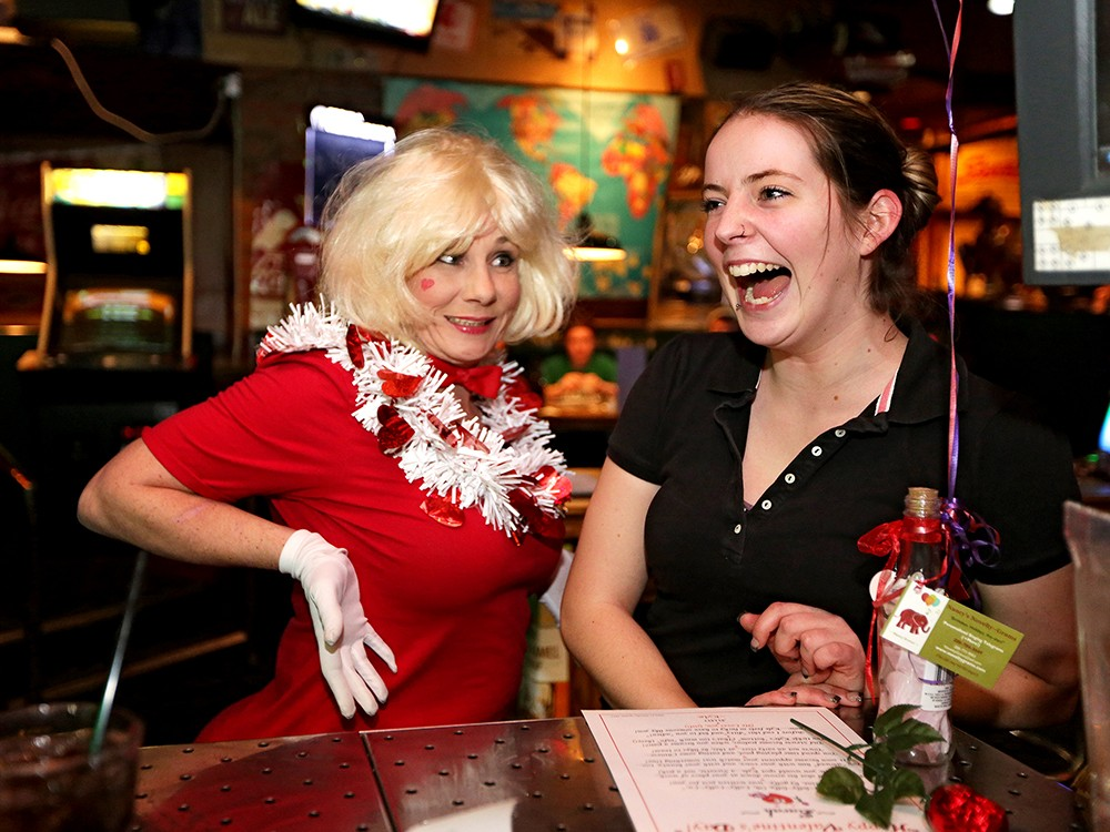Nancy Erchul, left, owner of Nancy\'s Novelty Grams, delivers a singing telegram for Sarah Burgess at Cricket\'s Steakhouse. - YOUNG KWAK