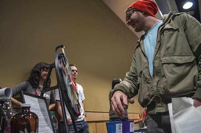 Jim Philp spins the PowderKeg prize wheel at the Snowlander Expo. - SARAH WURTZ