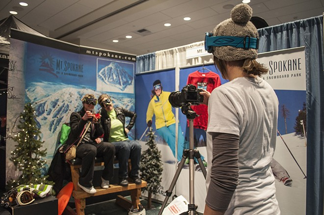 People get their photo taken on the Red Chair for a free beanie at the Mt. Spokane booth. - SARAH WURTZ