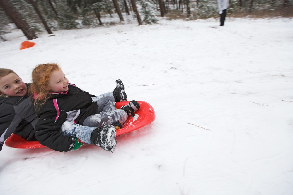 Nine-year-old Samuel Bakken, left, and his 7-year-old sister, Emily, sled at Underhill Park. - YOUNG KWAK