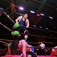 """Spokane Anarchy Wrestling at Swaxx North West Pro's JD Mason stands on Spokane Anarchy Wrestling's Rook """"Gladius"""" Kelly."""