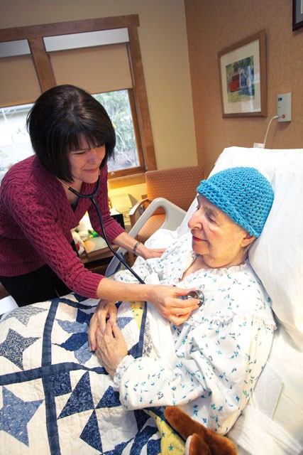 Nurse Manager LouAnn Ward checks 83-year-old Kathryn McCullochs chest at Hospice of Spokane. McCulloch has been a client at the hospice for three months. - YOUNG KWAK