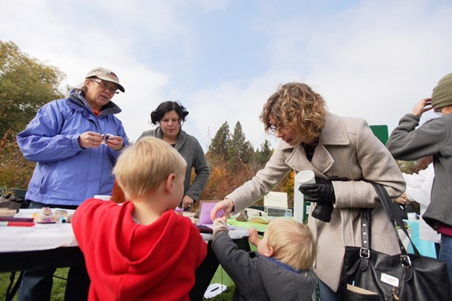 Olivia Schrock, right, help her 4-year-old son Carsten, left, and 2-year-old son Henrik with stamps at the Inland Northwest Land Trust booth. - YOUNG KWAK