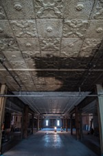 Ongoing renovations call for the tin ceilings to be restored, and the wooden floors on the fourth floor to be refinished. The brick walls with the old grocery store lettering will also remain intact.