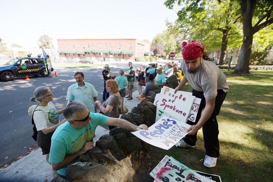 Organizer Brian Eister, right, hands Sam Evans a sign before a People's Climate March. - YOUNG KWAK