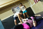 Owner Rick Little, left, shows Anjela Pink, front, and Mariah Pierce how to perform a shoulder lock while Julianna Peña looks on.