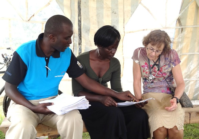 Partnering for Progress co-founder Stacy Mainer (right) talks with volunteers who helped distribut 4,500 mosquito nets in the area.