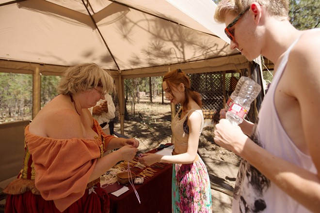 Patron Sam Berry, center, purchases a neck wrap from Pam Bristlin, left, as Hayden Hauck looks on. - YOUNG KWAK