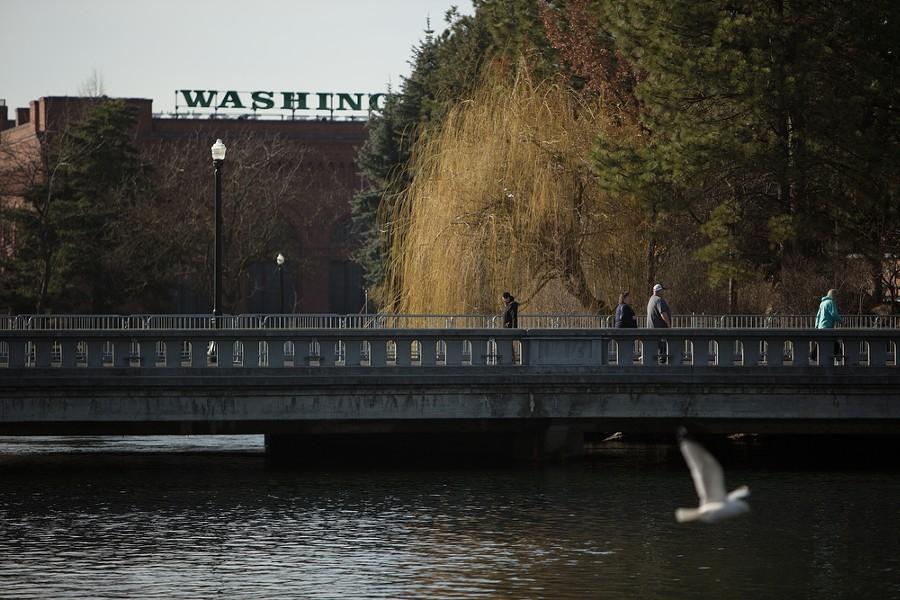 Pedestrians cross a bridge as a bird flies by. - YOUNG KWAK