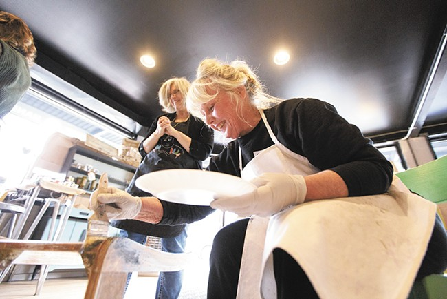 Penny Eaton, right, paints a chair as instructor Annette Tyrrell watches during a class at Artworks Spokane. - YOUNG KWAK