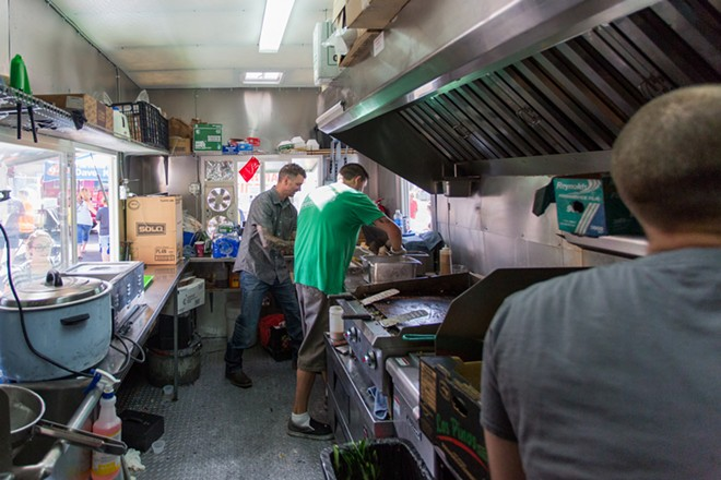 Steven Kitchnes, left, Mike Anderson  and Tymen Hofmann of Three Ninjas work quickly to prepare food for hungry customers at Food Truck Palooza. - MATT WEIGAND