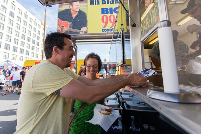 Alex Kokkoris, left and Rebecca Circkman get pulled pork from Nordic Smoke at Food Truck Palooza. - MATT WEIGAND