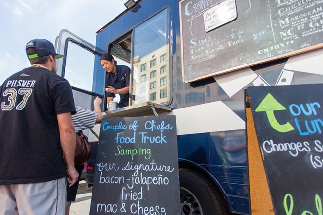 Joile Fomal, left, hands fried Macaroni to a customer at Food Truck Palooza. - MATT WEIGAND