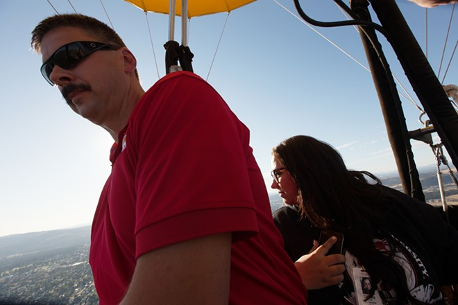 Passengers Jim Alford, left, and Tabina Al-Deik watch the landscape during a hot air balloon ride. - YOUNG KWAK