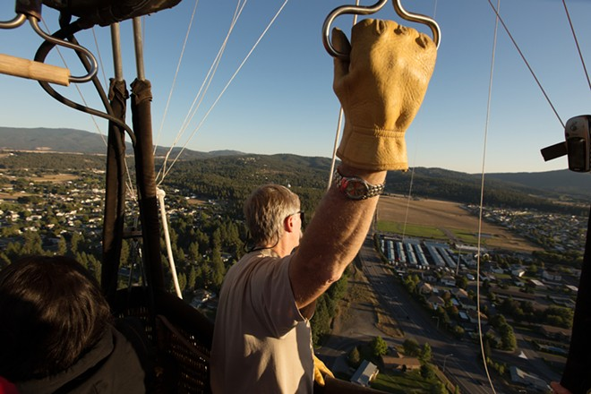 Pilot and Owner Forey Walter looks towards a landing spot at the South Pines Cemetery during a hot air balloon ride. - YOUNG KWAK