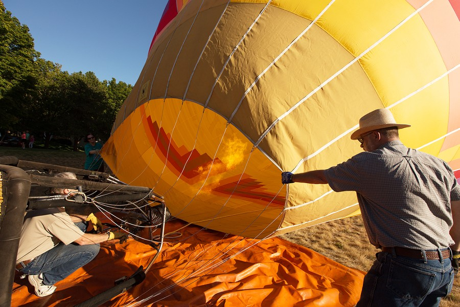 Pilot and Owner Forey Walter, left, turns on the burners as Gary Lynch, right, and Gail Bongiovanni hold onto the envelope before a hot air balloon ride. - YOUNG KWAK