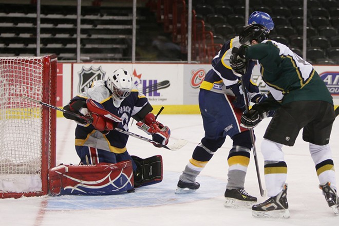 Spokane Police Department Officer Brad Moon, left, blocks a shot by Spokane County Sheriff's Office/Spokane Valley Police Department Deputy Clay Hilton, during the second period. Moon is the founder and organizer of the game. - YOUNG KWAK