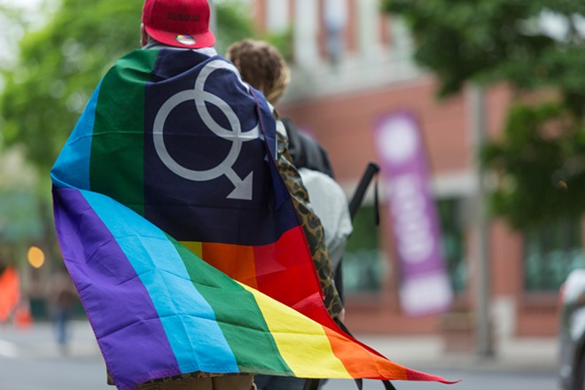 A man wears an equality flag at the Pride Parade. - MATT WEIGAND