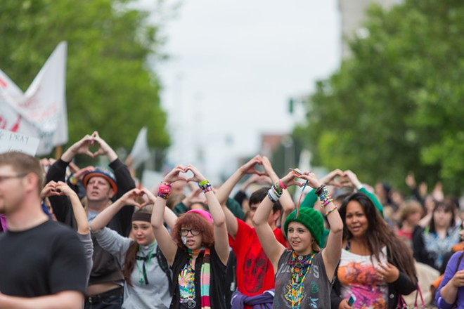 Parade participants hold up hearts as they reach the end of the route. - MATT WEIGAND