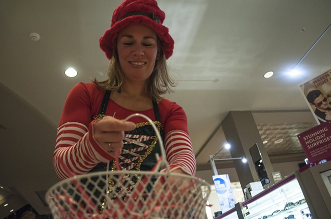 Andrea Worley, otherwise known as Rudi the Elf, hands out candy canes and jingle bells before Santa arrives. - SARAH WURTZ