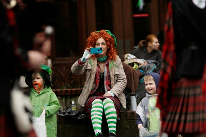 Jeannette Johnsen, center, takes video and photos of the Angus Scott Pipe Band as they pass by, as 4 year old Eli Kenagy, left, and 4 year old Max Rowland watch. - YOUNG KWAK