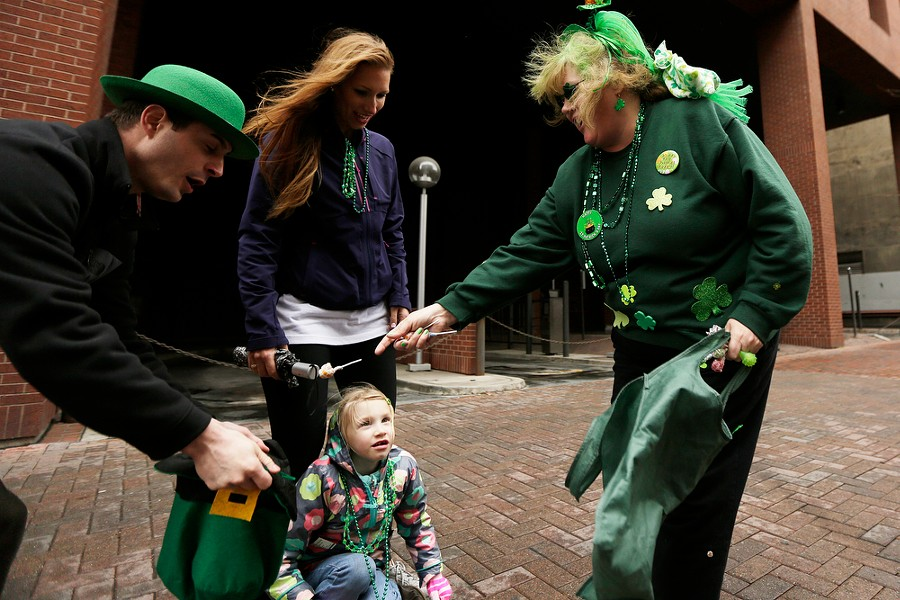 Karen Luiten, right, tosses candy into a hat held by Steve Daniels, left, as his 5 year old daughter Aniela, bottom, and Anick Lheureux watch. - YOUNG KWAK