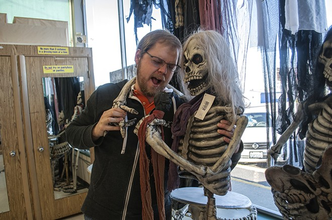 """Nick Jones poses for a photo with one of the store's """"rock 'n' roll"""" skeletons. - SARAH WURTZ"""