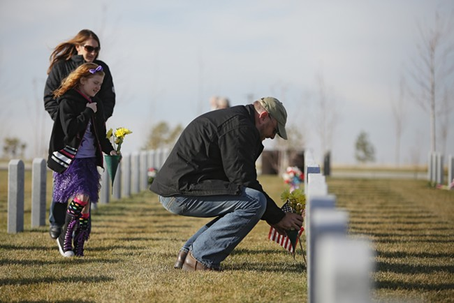 John McGarrigle, right, places flowers on his uncle U.S. Air Force (Ret.) John Minnihan's grave as Erica Johnson and her 9-year-old daughter Jamie look on, at the Washington State Veterans Cemetery. - YOUNG KWAK
