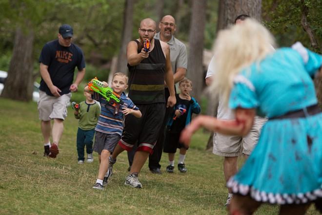 Race participant Pat Zantello, center, walks with 7-year-old Ahren Hurley, left, while shooting zombie Cara Lyonnais. - YOUNG KWAK