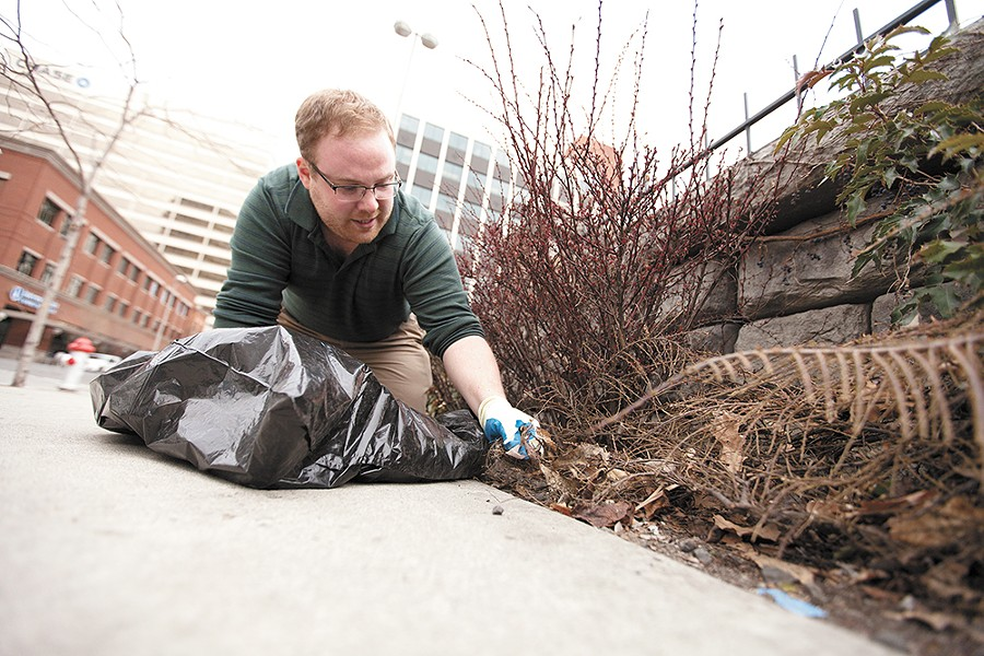 Reed Jessen picks up trash on North Howard Street as a result of a Crowdswell project. - YOUNG KWAK