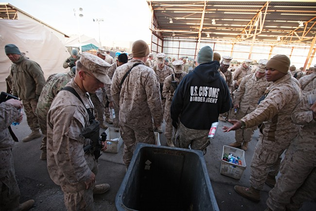 Returning military personnel from combat deployment in Afghanistan throw away unapproved items for travel. - YOUNG KWAK