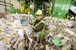 Rick McHenry removes items that don't belong from a bale of paper at Waste Management's SMaRT Center in Spokane on April 10.
