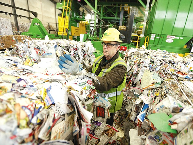 Rick McHenry removes items that don\'t belong from a bale of paper at Waste Management\'s SMaRT Center. - YOUNG KWAK