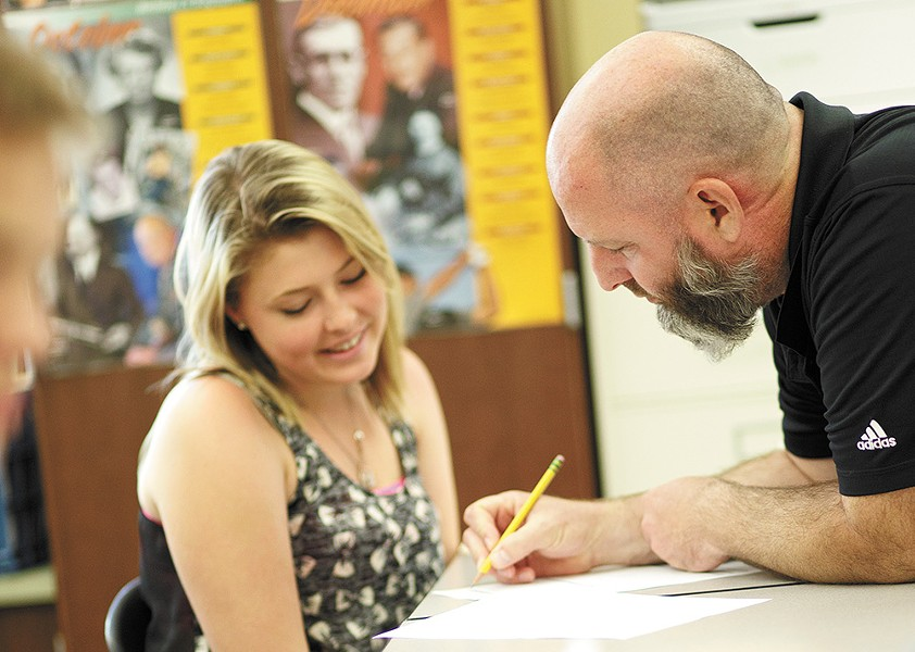 "Rogers High School teacher George Roth assists sophomore Taylour Freeland with her social studies assignment during ""ROW time,"" a 30-minute study hall made possible by a $3.7 million federal grant. - YOUNG KWAK"