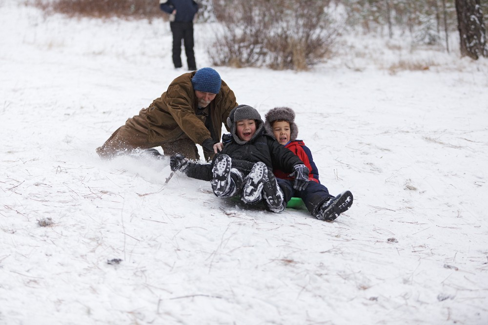 Ron Jones, left, pushes his grandsons, 6-year-old Desean Dunbar, center, and 7-year-old Zavion Lofton, down the slope at Underhill Park. - YOUNG KWAK
