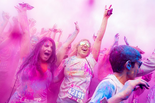 Runners during a dye throw at the post-race party at Run or Dye in Riverside State Park in May. - STEPHEN SCHLANGE