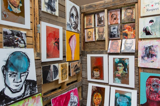 Ryan Desmond displays his paintings at his booth. - MATT WEIGAND