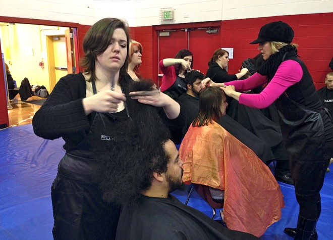 Savannah Mackey, a student at Paul Mitchell School in Spokane, gives Hector Ortiz a haircut in the Salvation Army gymnasium. - CLARKE HUMPHREY
